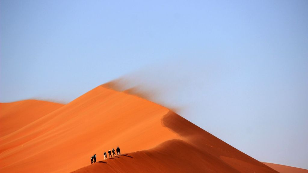 People walking up an orange sand dune